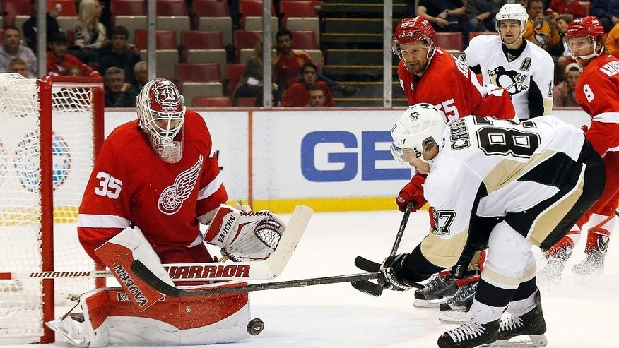 Detroit Red Wings goalie Jimmy Howard (35) stops a shot by Pittsburgh Penguins' Sidney Crosby (87) in the third period of a NHL preseason hockey game in Detroit Wednesday, Oct. 1, 2014. (AP Photo/Paul Sancya)