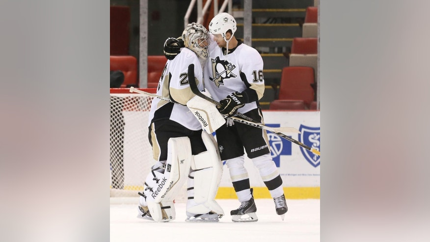 Pittsburgh Penguins goalie Marc-Andre Fleury (29) is congratulated by Brandon Sutter (16) after beating the Detroit Red Wings 2-0 in a NHL preseason hockey game in Detroit Wednesday, Oct. 1, 2014. (AP Photo/Paul Sancya)