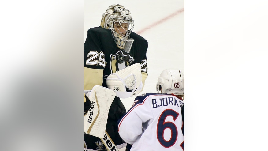 Pittsburgh Penguins goalie Marc-Andre Fleury (29) makes a save on Columbus Blue Jackets' Oliver Bjorkstrand in the third period of the NHL pre-season hockey game, Saturday, Sept. 27, 2014 in Pittsburgh. The Penguins won 2-1. (AP Photo/Keith Srakocic)