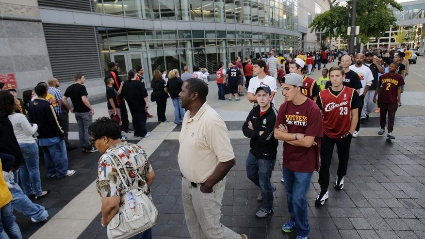 Cleveland Cavaliers fans line up outside the arena before the Cavaliers have an NBA scrimmage basketball game Wednesday, Oct. 1, 2014, in Cleveland. (AP Photo/Tony Dejak)
