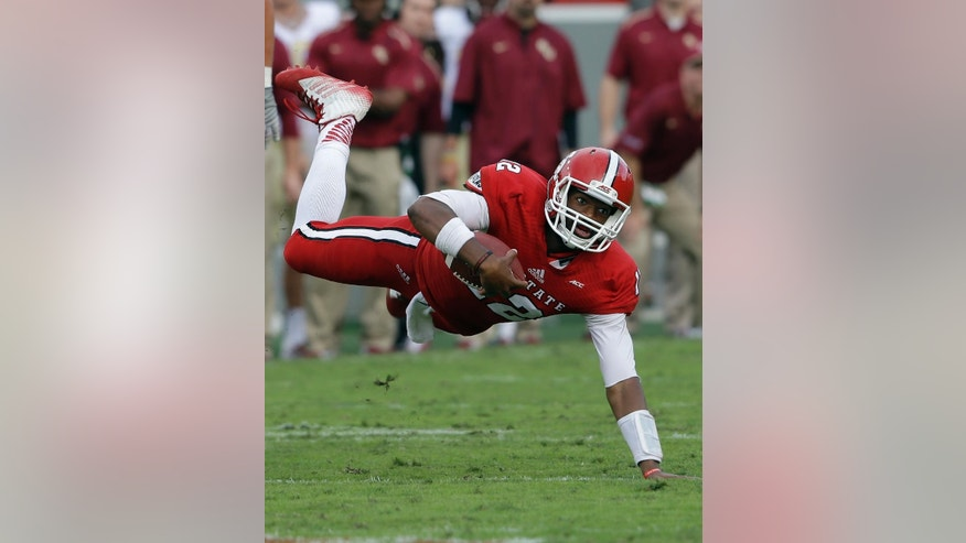 North Carolina State quarterback Jacoby Brissett gains some yardage while running the ball against Florida State during the second half of an NCAA college football game in Raleigh, N.C., Saturday, Sept. 27, 2014. Florida State won 56-41.(AP Photo/Gerry Broome)