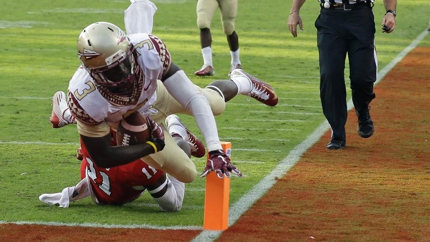 Florida State's Jesus Wilson (3) scores a touchdown as North Carolina State's Juston Burris (11) misses the tackle during the second half of an NCAA college football game in Raleigh, N.C., Saturday, Sept. 27, 2014. Florida State won 56-41.(AP Photo/Gerry Broome)