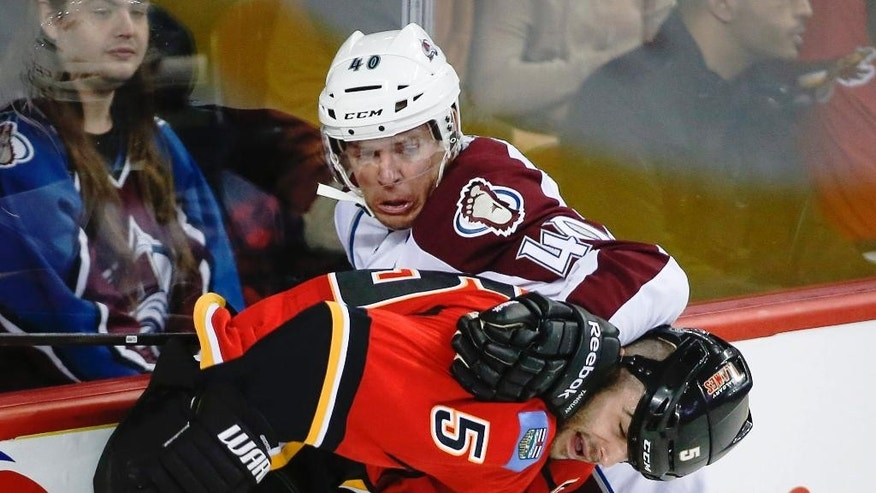 Colorado Avalanche's Alex Tanguay (40 )tries to get past Calgary Flames' Mark Giordano during second period NHL pre-season hockey action in Calgary,  Alberta, Tuesday, Sept. 30, 2014.(AP Photo/The Canadian Press, Jeff McIntosh)