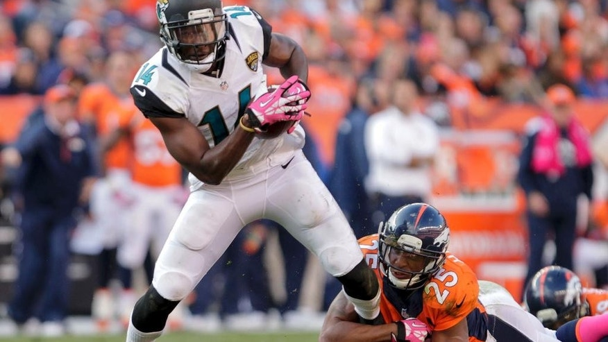 "FILE - In this Oct. 13, 2013, file photo, Jacksonville Jaguars wide receiver Justin Blackmon (14) tries to pull away from Denver Broncos cornerback Chris Harris (25) after catching pass during an NFL football game in Denver. Suspended Jaguars receiver Blackmon has checked into a voluntary treatment program and seems to be doing well. Coach Gus Bradley told The Associated Press on Wednesday, Oct. 1, 2014, that the former Oklahoma State star and 2012 first-round NFL draft pick ""is doing very well and he's learning a lot."" Bradley says he is getting updates from Blackmon's agent. (AP Photo/Joe Mahoney, FIle)"