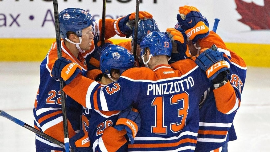 Edmonton Oilers' Keith Aulie (22), Mark Arcobello (26), Steven Pinizzotto (13), Martin Marincin (85) and Jesse Joensuu (6) celebrate a goal against the Arizona Coyotes during the second period of an NHL hockey preseason game, Wednesday, Oct. 1, 2014, in Edmonton, Alberta. (AP Photo/The Canadian Press, Jason Franson)