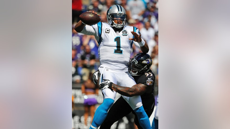 Carolina Panthers quarterback Cam Newton (1) gets a pass off under pressure from Baltimore Ravens outside linebacker Terrell Suggs (55) during the first half of an NFL football game in Baltimore, Sunday, Sept. 28, 2014. (AP Photo/Evan Vucci)