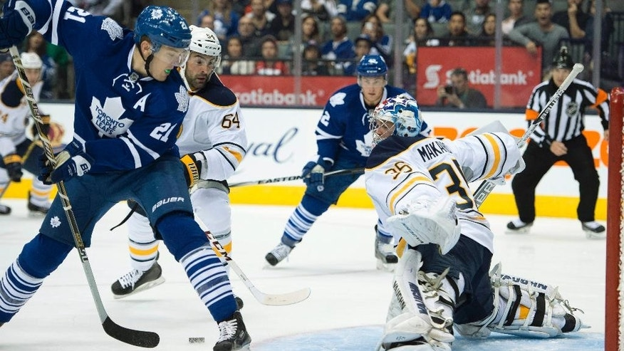 Buffalo Sabres goaltender Andrey Makarov, right,  makes a save on Toronto Maple Leafs James van Riemsdyk (21) as Sabres Nick Petrecki (64) looks on during second period pre-season NHL action in Toronto on Sunday, Sept. 28, 2014.(AP Photo/The Canadian Press, Frank Gunn)