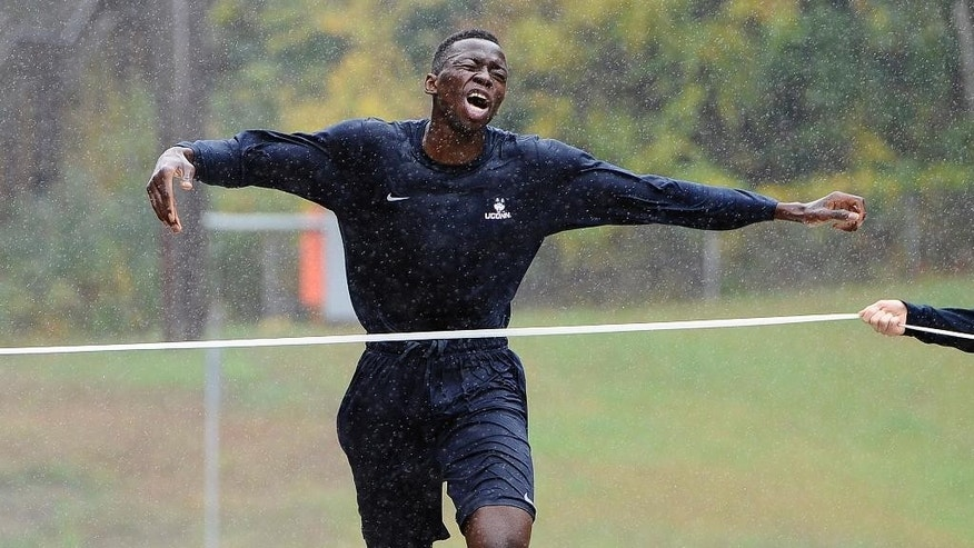 Connecticut NCAA college basketball player Amida Brimah crosses the finish line with a time of 20:22 as the first player to finish the Husky Run, Wednesday, Oct. 1, 2014, in Storrs, Conn. (AP Photo/Jessica Hill)