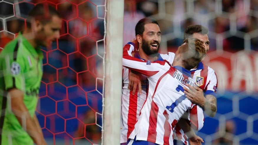 Atletico's Arda Turan, centre, celebrates with Atletico's Antoine Griezmann after scoring during the Group A Champions League soccer match between Atletico de Madrid and Juventus at the Vicente Calderon stadium in Madrid, Spain, Wednesday Oct. 1, 2014. (AP Photo/Andres Kudacki)
