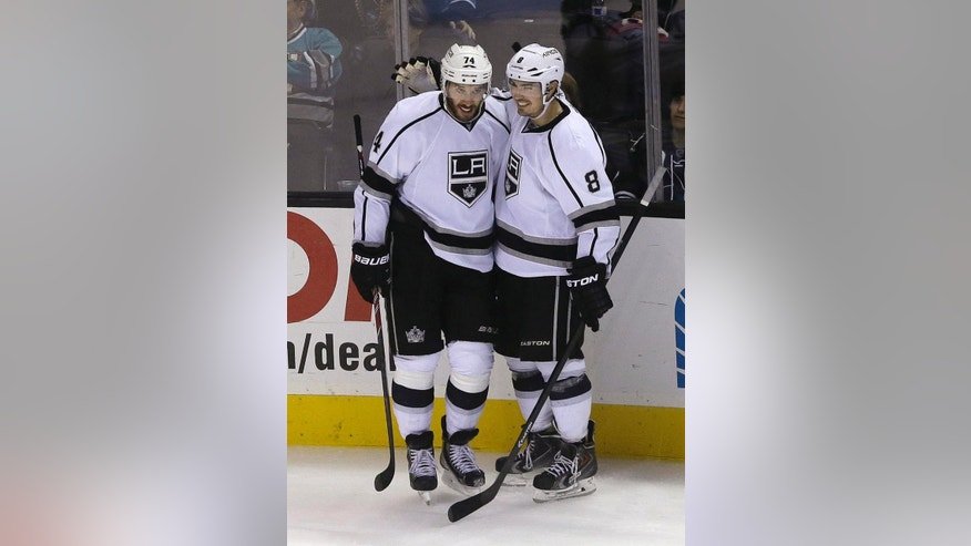Los Angeles Kings left wing Dwight King, left, is congratulated by defenseman Drew Doughty (8) after scoring against the San Jose Sharks during the third period of an NHL preseason hockey game in San Jose, Calif., Tuesday, Sept. 30, 2014. The Kings won 4-1. (AP Photo/Jeff Chiu)