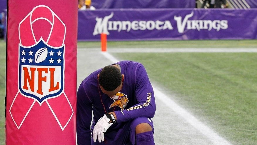 "FILE - In this Oct. 13, 2013, file photo, Minnesota Vikings wide receiver Joe Webb prays at the base of a goal post wrapped to promote breast cancer awareness before an NFL football game against the Carolina Panthers in Minneapolis. The NFL's fourth annual ""Breast Cancer Awareness Month"" kicks off Thursday night, Oct. 2, 2014,  with the Viking at the Packers  and runs through October.   (AP Photo/Ann Heisenfelt, File)"