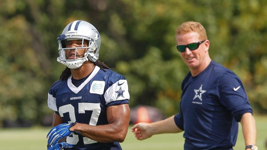 Dallas Cowboys defensive back C.J. Spillman, left,  walks past head coach Jason Garrett during a practice session Thursday, October 2, 2014 at the team's headquarters in Irving, Texas. With his coach's backing,  Spillman returned to the Cowboys practice field as he awaits the results of a police investigation into his role in an alleged sexual assault last month at a suburban Dallas hotel. (AP Photo/Tim Sharp)