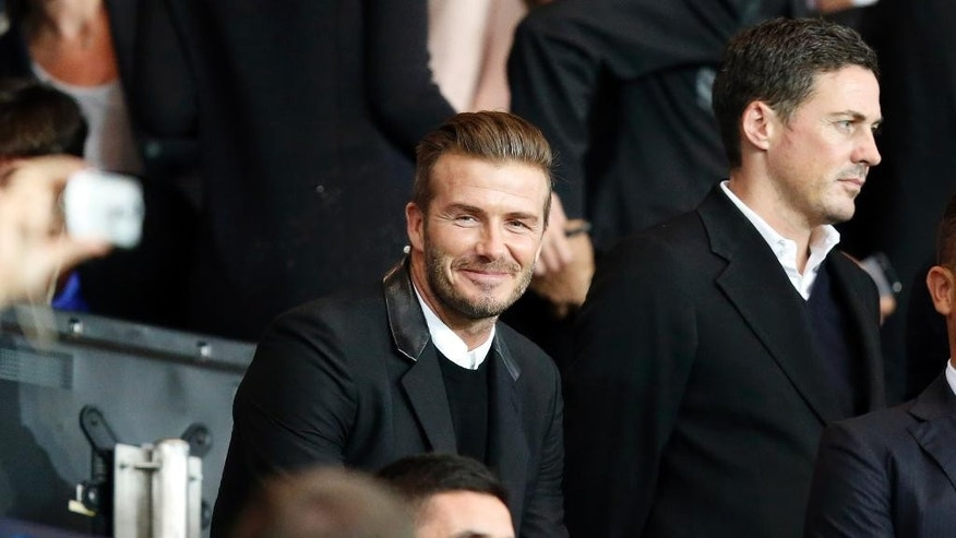 David Beckham, center, smiles to the photographers as he arrives to attend the the Champions League Group F soccer match between Paris Saint German and Barcelona at Parc des Princes stadium in Paris, France, Tuesday, Sept. 30, 2014. (AP Photo/Michel Euler)