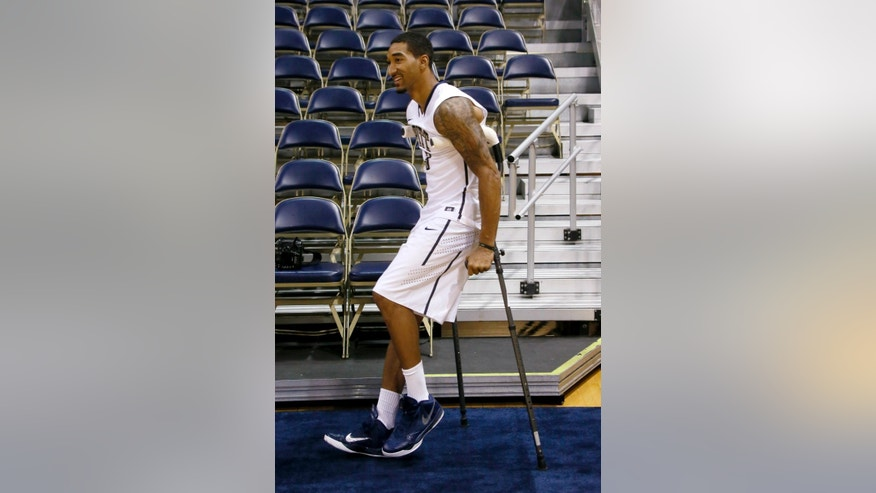 Pittsburgh guard Cameron Wright comes onto the court using crutches during the school's annual media day for the upcoming NCAA college basketball season on Thursday, Oct. 2, 2014, in Pittsburgh. Wright recently injured his ankle and is expected to be out for an undertermined amount of time. (AP Photo/Keith Srakocic)