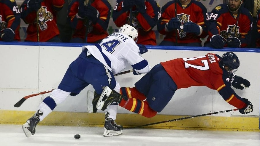 Tampa Bay Lightning Cedric Paquette (54) and Florida Panthers' Colby Robak (47) battle for the puck during the first period of a NHL hockey game in Sunrise, Fla., Thursday, Oct. 2, 2014. (AP Photo/J Pat Carter)