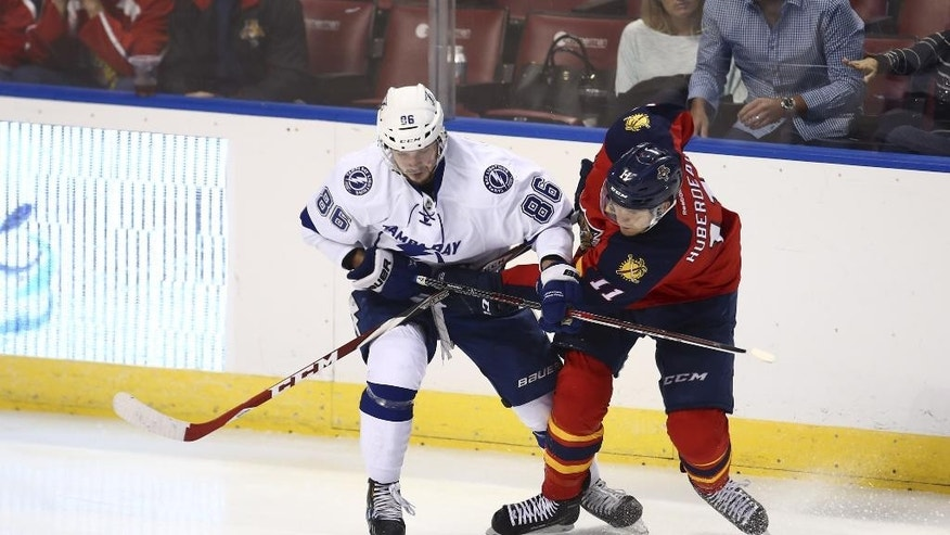 Tampa Bay Lightning's Nikita Kucherov (86) and Florida Panthers' Jonathan Huberdeau (11) battle for the puck during the third period of a preseason NHL hockey game in Sunrise, Fla., Thursday, Oct. 2, 2014. The Lightning won 3-0. (AP Photo/J Pat Carter)