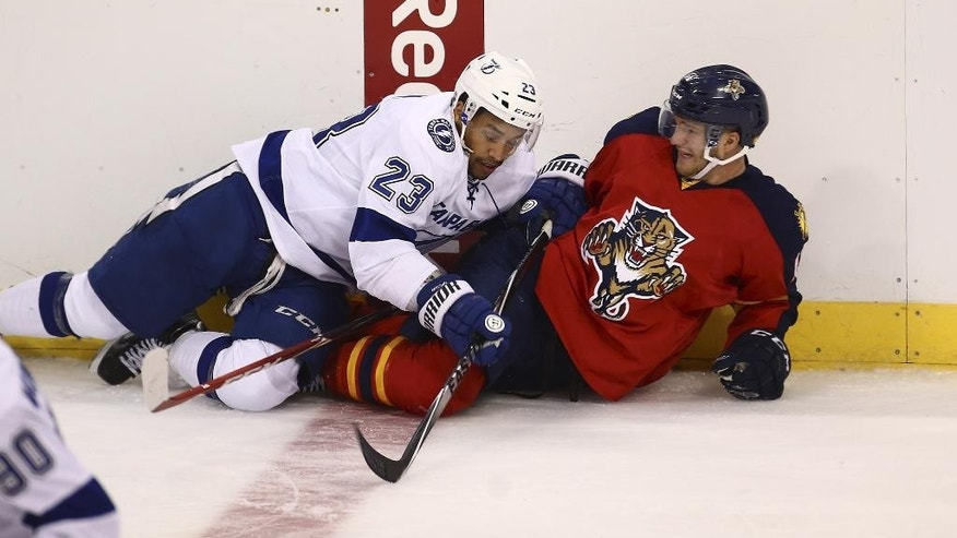 Tampa Bay Lightning's J.T. Brown (23) and Florida Panthers' Jonathan Huberdeau (11) fall to the ice as they battle for the puck during the second period of a NHL hockey game in Sunrise, Fla., Thursday, Oct. 2, 2014. (AP Photo/J Pat Carter)