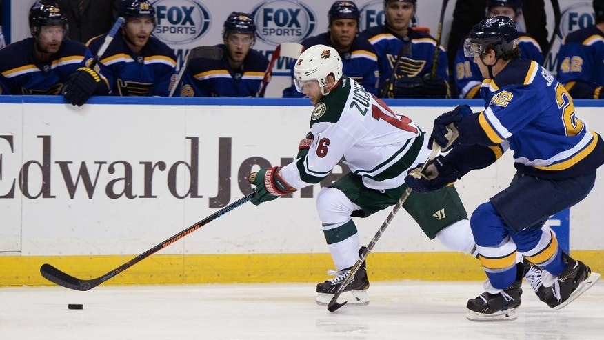 Minnesota Wild's Jason Zucker (16) skates by St. Louis Blues' Kevin Shattenkirk (22) during the first period of a preseason NHL hockey game, Thursday, Oct. 2, 2014, in St. Louis. (AP Photo/Bill Boyce)