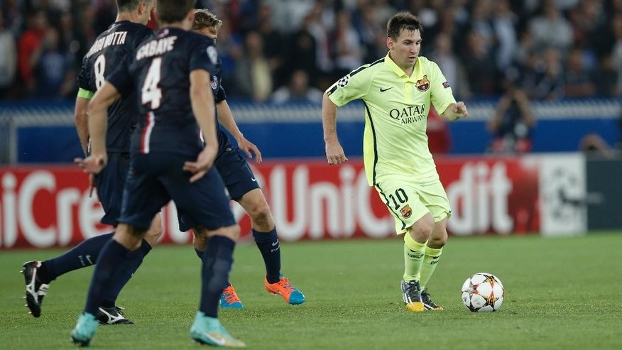 Barcelona's Lionel Messi, right, is faced by a wall of PSG defenders during the Champions League soccer match between PSG and Barcelona, at the Parc des Princes stadium, in Paris, Tuesday, Sept. 30, 2014. (AP Photo/Christophe Ena)