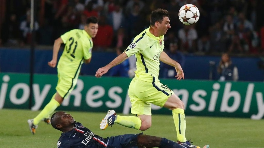 Barcelona's Lionel Messi, right, challenges for the ball with PSG's Blaise Matuidi, down, during the Champions League Group F soccer match between Paris Saint German and Barcelona at Parc des Princes stadium in Paris, France, Tuesday, Sept. 30, 2014. (AP Photo/Michel Euler)
