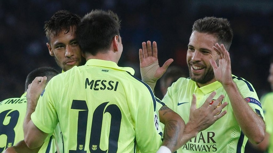 Barcelona's Lionel Messi, 10, is congratulated by teammates, Neymar, left, and Jordi Alba, right, during the Champions League Group F soccer match between Paris Saint German and Barcelona at Parc des Princes stadium in Paris, France, Tuesday, Sept. 30, 2014. (AP Photo/Michel Euler)