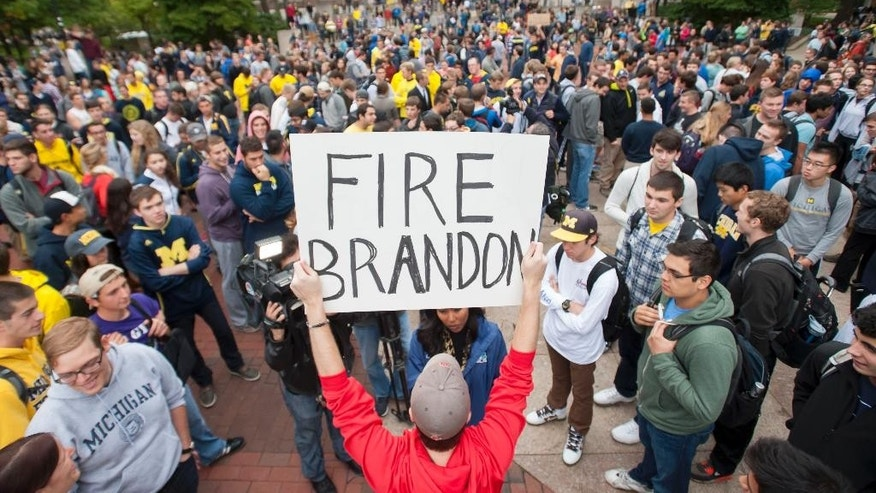 "In a Sept. 30, 2014 photo, law student Edward Mears holds a ""Fire Brandon"" sign during a protest on the campus of the University of Michigan over the recent football game against Minnesota where quarterback Shane Morris was left in the game after receiving a concussion. About 1,000 University of Michigan students marched to the home of school President Mark Schlissel to protest against the performance of athletic director Dave Brandon and football coach Brady Hoke.  (AP Photo/The Detroit News, David Guralnick)"