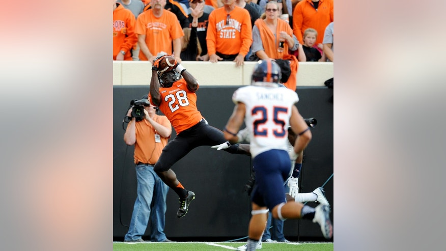 FILE - In this Sept. 13, 2014, file photo, UTSA safety Mauricio Sanchez (25) races toward Oklahoma State wide receiver James Washington (28) as he catches a touchdown pass from quarterback Daxx Garman during the first half of an NCAA college football game in Stillwater, Okla. Washington and Tyreek Hill have emerged as deep threats for the rapidly improving Daxx Garman.  (AP Photo/Brody Schmidt, File)