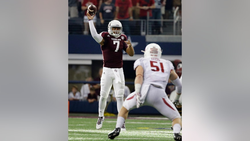 Texas A&M quarterback Kenny Hill (7) passes under pressure from Arkansas linebacker Brooks Ellis (51) in the second half of an NCAA college football game, Saturday, Sept. 27, 2014, in Arlington, Texas. The Aggies won in overtime 35-28. (AP Photo/Tony Gutierrez)