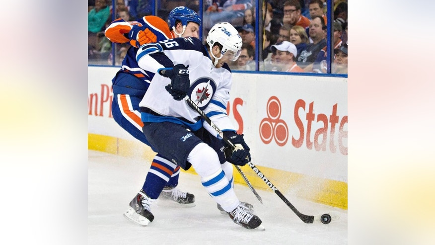 Edmonton Oilers goalie Viktor Fasth (35) and Mark Fayne (5) celebrate a win over the Winnipeg Jets during an NHL hockey game in Edmonton, Alberta, on Monday, Sept. 29, 2014. (AP Photo/The Canadian Press, Jason Franson)