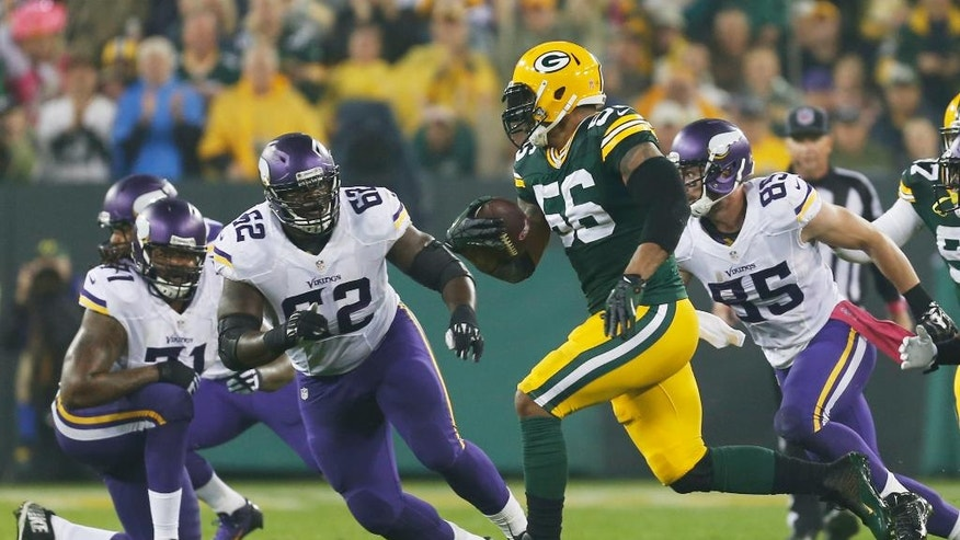 Green Bay Packers' Julius Peppers runs back an interception 49-yards for a touchdown during the first half of an NFL football game against the Minnesota Vikings Thursday, Oct. 2, 2014, in Green Bay, Wis. (AP Photo/Mike Roemer)