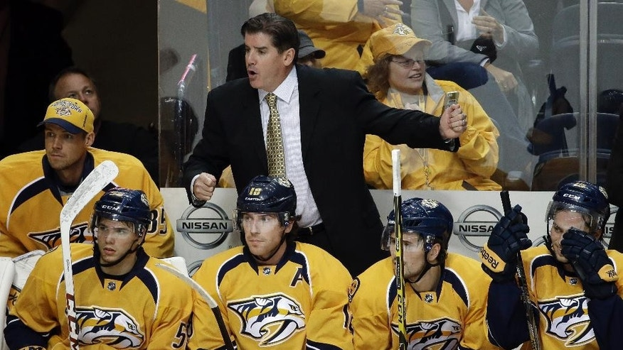 In this Sept. 25, 2014 photo, Nashville Predators head coach Peter Laviolette directs his players in a preseason NHL hockey game against the Tampa Bay Lightning in Nashville, Tenn. Laviolette begins his career with the Predators as only the second head coach in the team's history, hoping to juice up their offensive production. (AP Photo/Mark Humphrey)