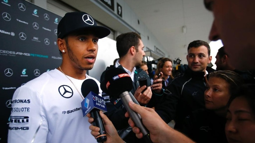 Mercedes driver Lewis Hamilton of Britain speaks during an interview outside his team's garage at the Suzuka Circuit in Suzuka, central Japan, Thursday, Oct. 2, 2014. Hamilton will be aiming to complete a hat trick of wins and extend his narrow Formula One championship lead over teammate Nico Rosberg at Sunday's Japanese Grand Prix, a race that has been dominated by Red Bull's Sebastian Vettel in recent years. (AP Photo/Shizuo Kambayashi)