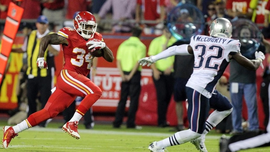 Kansas City Chiefs running back Knile Davis, left, runs for a 48-yard gain as New England Patriots free safety Devin McCourty defends during the second quarter of an NFL football game Monday, Sept. 29, 2014, in Kansas City, Mo. (AP Photo/Ed Zurga)