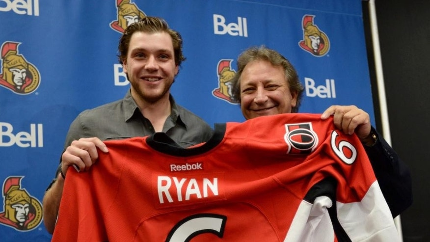 Bobby Ryan, left, and Eugene Melnyk, owner of the Ottawa Senators NHL hockey team, hold Ryan's jersey at a news conference Thursday, Oct. 2, 2014, in Ottawa. Ryan was signed to a seven-year, $50.75 million contract extension.  (AP Photo/The Canadian Press, Sean Kilpatrick)