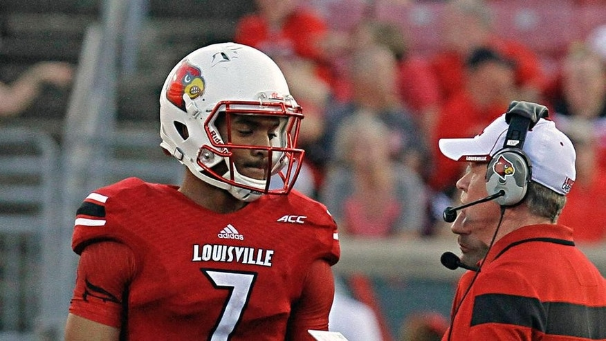 Louisville coach Bobby Petrino, right, talks with freshman quarterback Reggie Bonnafon (7) during a timeout late in the NCAA college football game against Wake Forest in Louisville, Ky., Saturday, Sept. 27, 2014. Louisville beat Wake Forest 20-10. (AP Photo/Garry Jones)