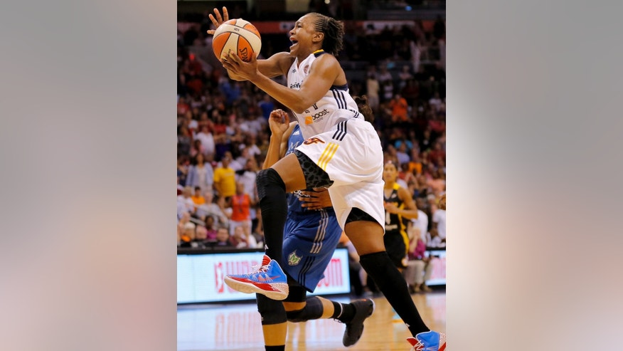 FILE - In this July 19, 2014, file photo, East's Tamika Catchings, of the Indiana Fever, scores the game winning basket during the overtime period of the WNBA All-Star basketball game in Phoenix. Three-time Olympic gold medalist Tamika Catchings says she will retire after the 2016 Rio Games. The Indiana Fever star confirmed Friday, Oct. 3, 2014,  in an email to The Associated Press that she will call it quits after the 2016 Olympics, but plans to play two more WNBA seasons. (AP Photo/Matt York, File)