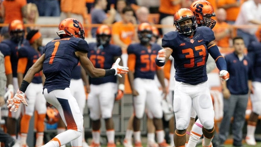 Syracuse's Julian Whigham, left, and Marqez Hodge, right, celebrate after sacking Louisville quarterback Reggie Bonnafon in the first quarter of an NCAA college football in Syracuse, N.Y., Friday, Oct. 3, 2014. (AP Photo/Nick Lisi)