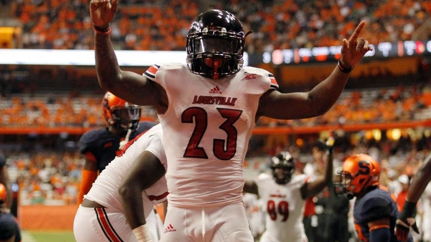 Louisville's Brandon Radcliff celebrates scoring a touchdown in the first quarter of an NCAA college football game against Syracuse in Syracuse, N.Y., Friday, Oct. 3, 2014. (AP Photo/Nick Lisi)