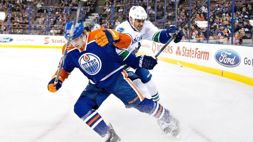 Vancouver Canucks' Tom Sestito (29) and Edmonton Oilers' Bogdan Yakimov (39) collide during the first period of a preseason NHL hockey hockey game Thursday, Oct. 2, 2014, in Edmonton, Alberta. (AP Photo/The Canadian Press, Jason Franson)