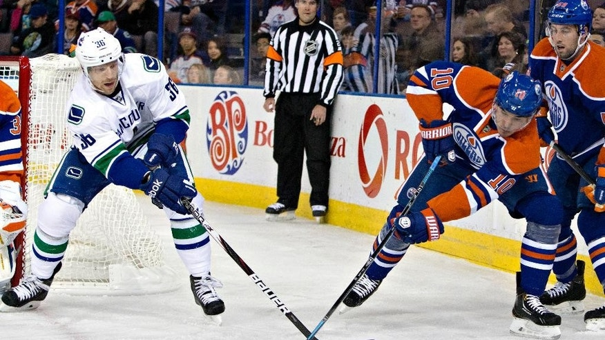 Vancouver Canucks' Jannik Hansen (36) and Edmonton Oilers' Nail Yakupov (10) battle for the puck during the first period of a preseason NHL hockey hockey game Thursday, Oct. 2, 2014, in Edmonton, Alberta. (AP Photo/The Canadian Press, Jason Franson)