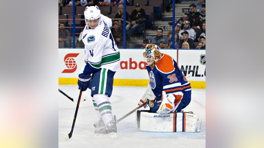 Vancouver Canucks' Alex Burrows (14) screens Edmonton Oilers goalie Viktor Fasth (35) as Fasth makes the save during the first period of a preseason NHL hockey hockey game Thursday, Oct. 2, 2014, in Edmonton, Alberta. (AP Photo/The Canadian Press, Jason Franson)