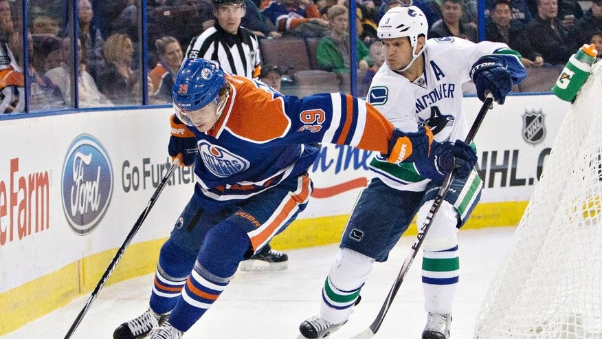 Vancouver Canucks' Kevin Bieksa (3) chases Edmonton Oilers' Bogdan Yakimov (39) during the second period of a preseason NHL hockey hockey game Thursday, Oct. 2, 2014, in Edmonton, Alberta. (AP Photo/The Canadian Press, Jason Franson)