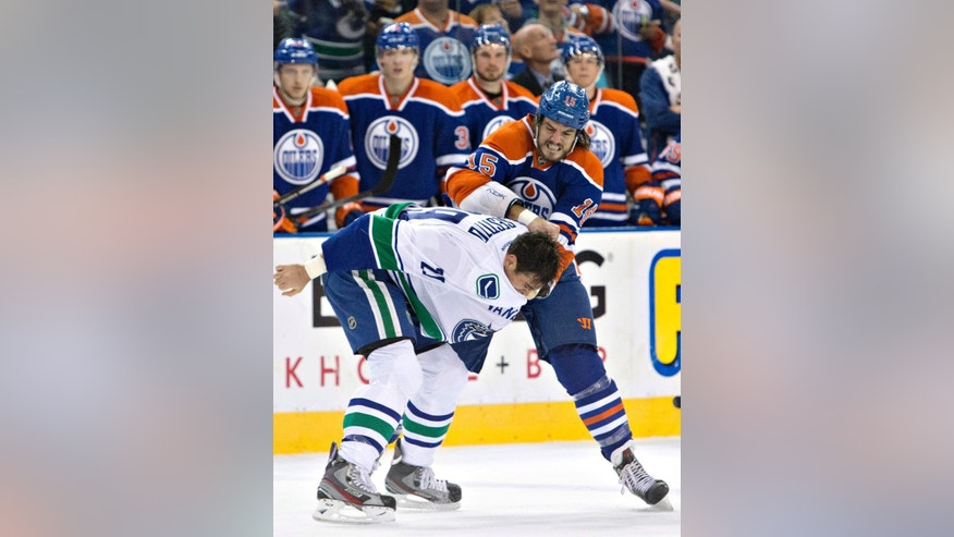 Vancouver Canucks' Tom Sestito (29) fights Edmonton Oilers' Kevin Westgarth (15) during the second period of a preseason NHL hockey hockey game Thursday, Oct. 2, 2014, in Edmonton, Alberta. (AP Photo/The Canadian Press, Jason Franson)