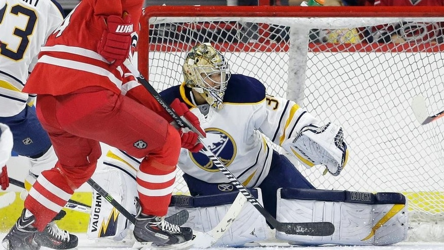 Carolina Hurricanes' Andrej Sekera (4), of Slovakia, tries to score against Buffalo Sabres goalie Michal Neuvirth during the first period of a preseason NHL hockey game in Raleigh, N.C., Friday, Oct. 3, 2014. (AP Photo/Gerry Broome)