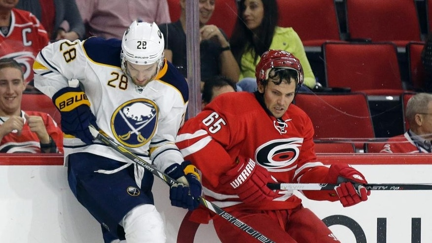 Buffalo Sabres' Zemgus Girgensons (28) and Ron Hainsey (65) struggle for possession of the puck during the second period of a preseason NHL hockey game in Raleigh, N.C., Friday, Oct. 3, 2014. (AP Photo/Gerry Broome)