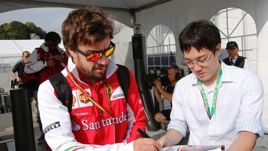 Ferrari driver Fernando Alonso of Spain gives a fan his autograph upon arrival at the Suzuka Circuit for the first practice session for Sunday's Japanese Formula One Grand Prix in Suzuka, central Japan, Friday, Oct. 3, 2014. (AP Photo/Shizuo Kambayashi)