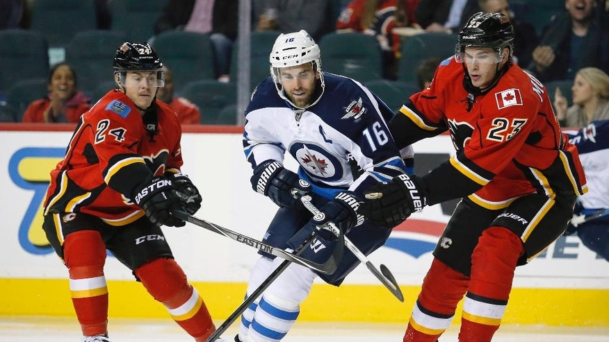 Winnipeg Jets Andrew Ladd, center, tries to squeeze past Calgary Flames Jiri Hudler, left, from the Czech Republic, and Sean Monahan during the second period of an NHL pre-season hockey game, Thursday, Oct. 2, 2014 in Calgary, Alberta. (AP Photo/The Canadian Press, Jeff McIntosh)