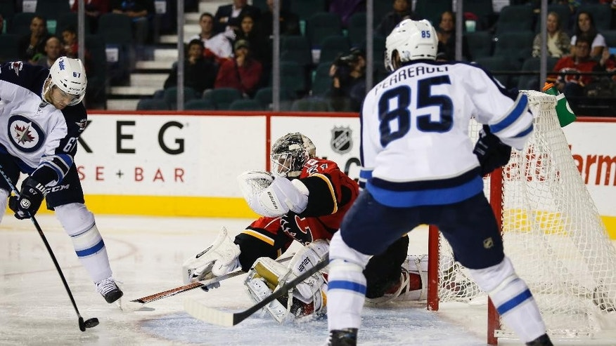 Winnipeg Jets Michael Frolik, left, from the Czech Republic, tries to get the puck past Calgary Flames goalie Karri Ramo, center, from Finland, as Jets Peter Stoykewych looks on during the second period of an NHL pre-season hockey game, Thursday, Oct. 2, 2014 in Calgary, Alberta. (AP Photo/The Canadian Press, Jeff McIntosh)
