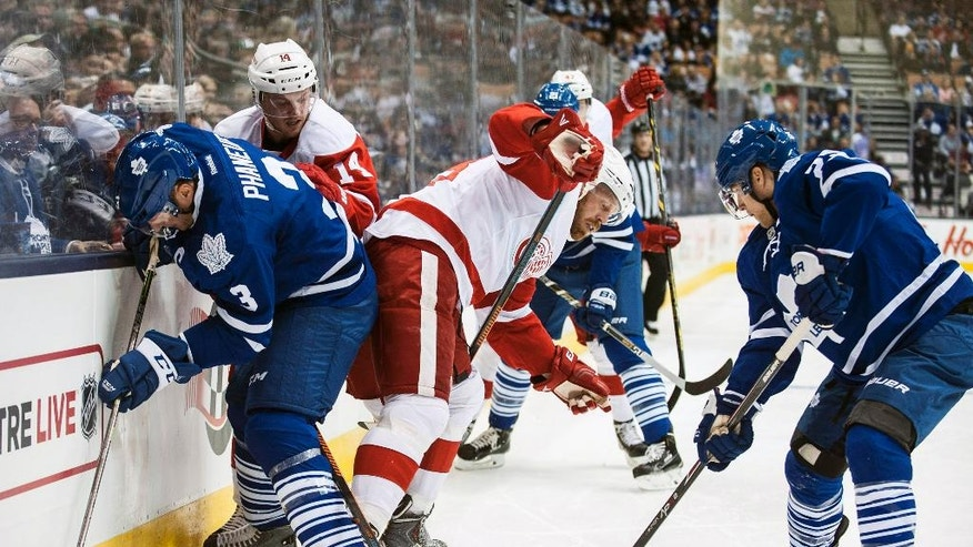 Detroit Red Wings' Johan Franzen, center, loses the puck to Toronto Maple Leafs' Mike Santorelli, right, during first-period preseason NHL hockey game action in Toronto, Friday, Oct. 3, 2014. (AP Photo/The Canadian Press, Aaron Vincent Elkaim)
