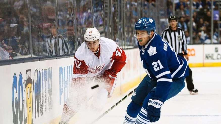 Detroit Red Wings' Alexey Marchenko, left, takes the puck downice past Toronto Maple Leafs' James van Riemsdyk during first-period preseason NHL hockey game action in Toronto, Friday, Oct. 3, 2014. (AP Photo/The Canadian Press, Aaron Vincent Elkaim)
